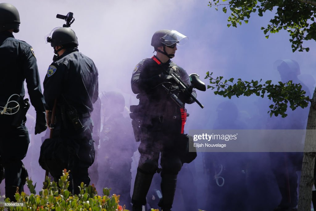 Police stand guard at MLK Jr. Park as smoke from a purple smoke grenade filters surrounds them on August 27, 2017 in Berkeley, California. The park became a center of left-wing protest when hundreds of people opposed to President Trump and hundreds more aligned with Antifa descended on it after a planned right-wing rally was cancelled.
