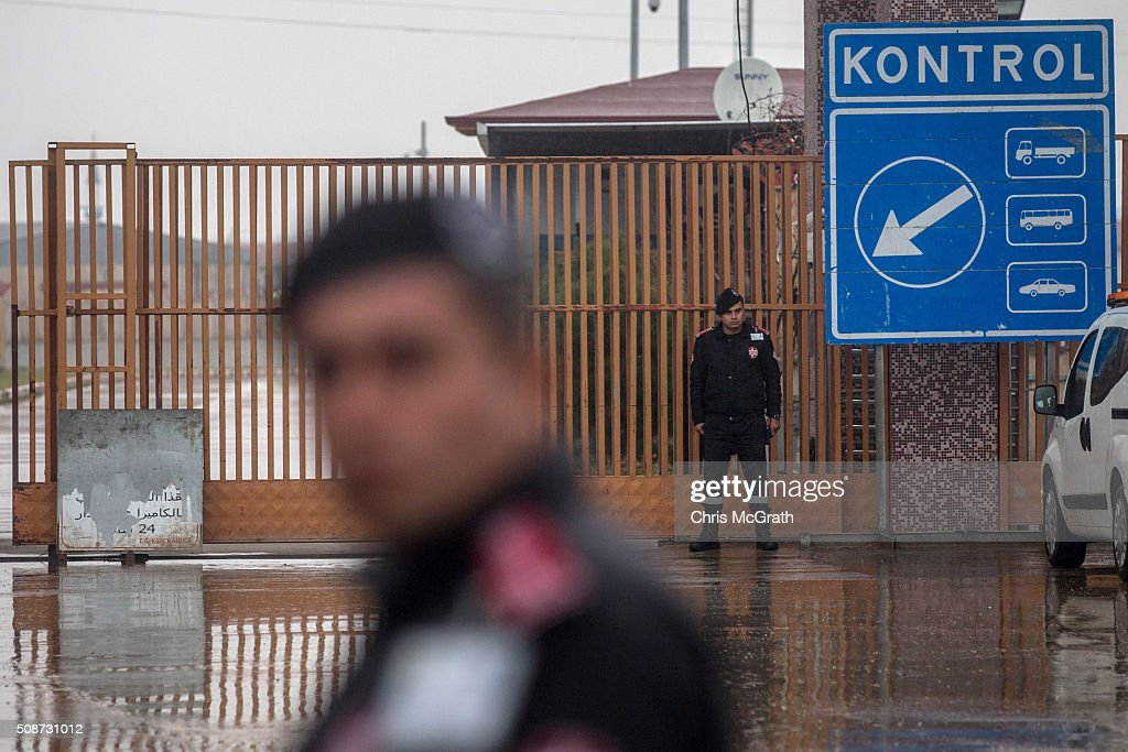 Police stand guard at the closed Turkish border gate on February 6, 2016 in Kilis, Turkey. According to Turkish officials some 35,000 Syrian refugees have massed on the Syrian/Turkish border after fleeing Russian airstrikes and a regime offensive surrounding the city of Aleppo in northern Syria.