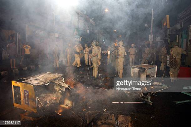 Police stand guard by burning debris after shops were set afire by a mob in the intervening night of 10th and 11th August during a curfew on August...
