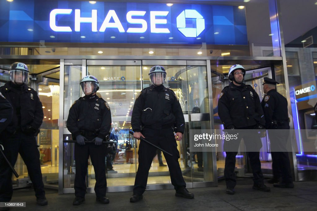 Police stand guard in front of a Chase bank entrance during a May Day march on May 1, 2012 in New York City. Occupy Wall Street demonstrators joined labor groups in a march through downtown to protest economic injustice and observe International Labor Day.