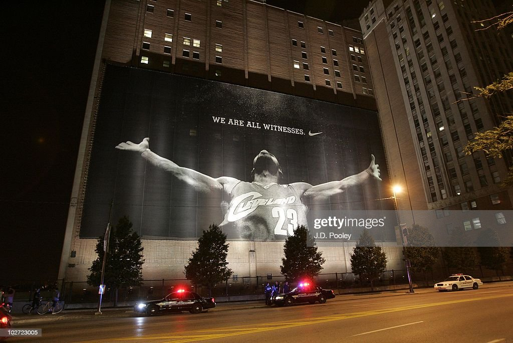 Police stand guard near a larger than life photograph of <a gi-track='captionPersonalityLinkClicked' href=/galleries/search?phrase=LeBron+James&family=editorial&specificpeople=201474 ng-click='$event.stopPropagation()'>LeBron James</a> after the announcement that James will play next season for the Miami Heat July 8, 2010 in Cleveland, Ohio. The two-time Most Valuable Player made the choice to play for Miami next season.