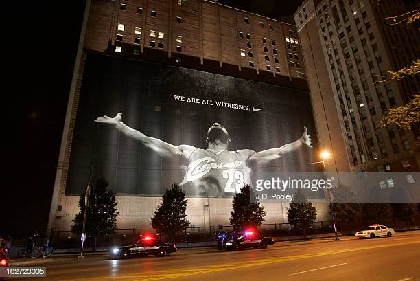 Police stand guard near a larger than life photograph of LeBron James after the announcement that James will play next season for the Miami Heat July...