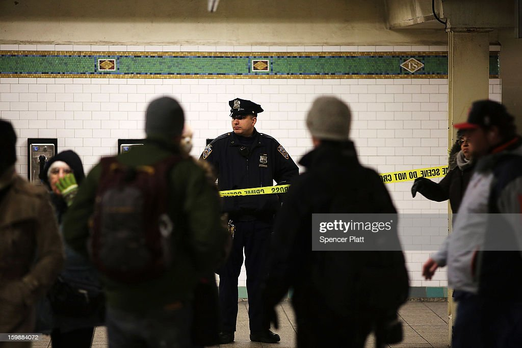 Police stand guard near where the body of an apparent suicide victim lies at a subway station in Times Square on January 22, 2013 in New York City. New York City has been experiencing a rash of high-profile incidents involving individuals being hit by trains in suicides, accidents and people being pushed to their deaths.