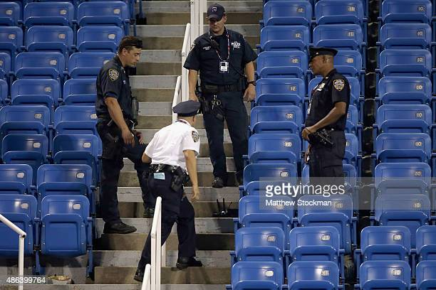 Police stand guard next to a drone after it crashed into the stands in Louis Armstrong Stadium during the during their Women's Singles Second Round...