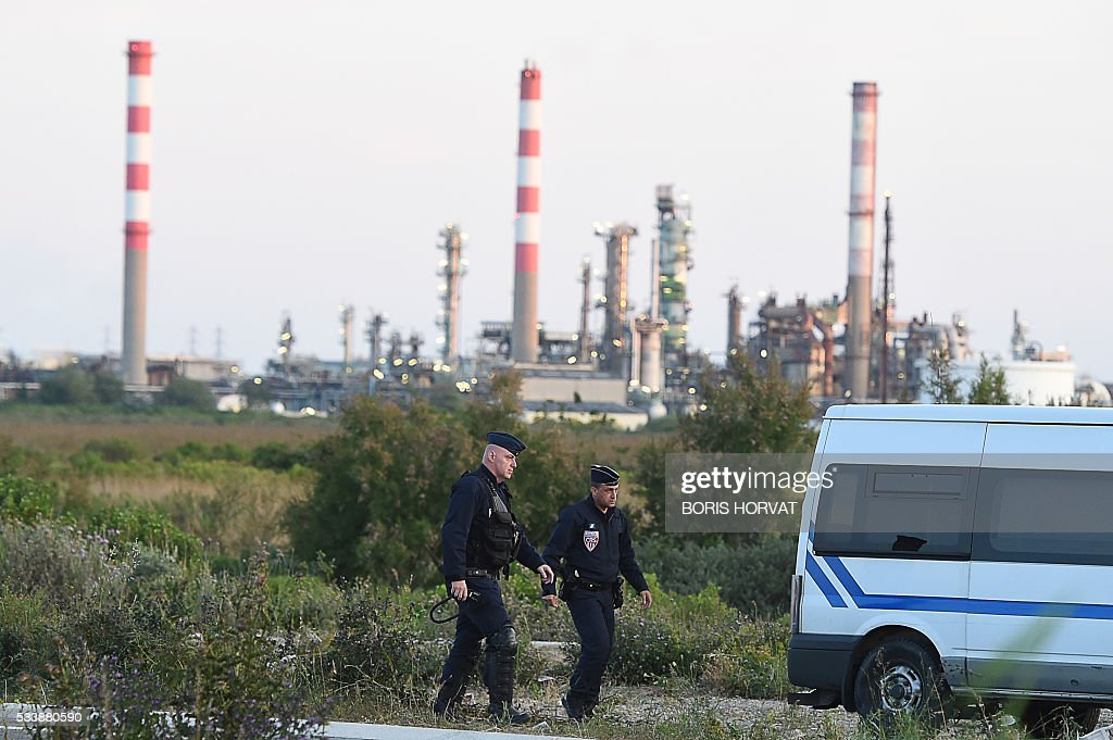 Police stand guard on a road near the fuel depots in Fos-sur-Mer, southern France, on May 24, 2016, after freeing access to the site which was blocked by workers' union members opposed to government labour reforms. Petrol shortages caused long tailbacks of motorists in parts of France on May 23 as protesters angry over government labour reforms blockaded some of the country's oil refineries and fuel depots. The action was the latest in three months of strikes and protests against the reform, which has set the Socialist government against some of its traditional supporters and sometimes sparked violence. HORVAT