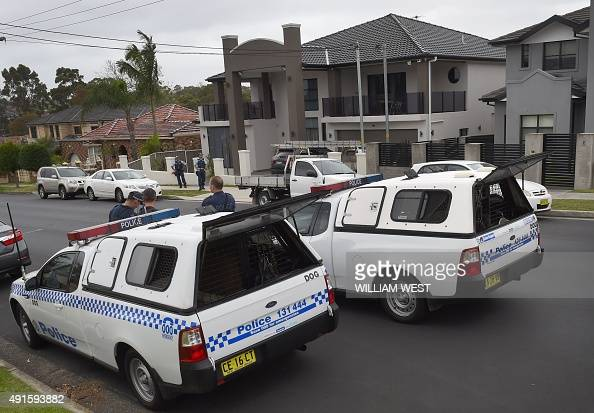 Police stand guard outside a house as four people were arrested over the terrorlinked murder of a police employee after coordinated raids by more...
