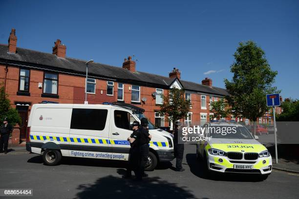 Police stand guard outside a property on Dorset Avenue in Moss Side Manchester on May 26 following a raid on a residential property as their...