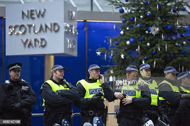 Police stand guard outside New Scotland Yard during a student march against university fees in Central London on November 19 2014 The demonstration...