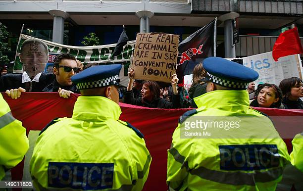 Police stand guard outside the National Party Annual Conference as protesters demonstrate at Sky City Convention Centre on July 22 2012 in Auckland...