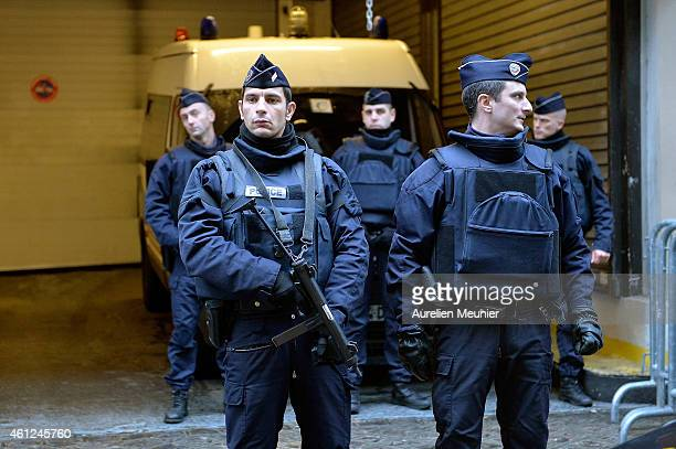 Police stand guard outside the offices of French daily newspaper Liberation as the remaining members of the Charlie Hebdo editorial staff arrive for...