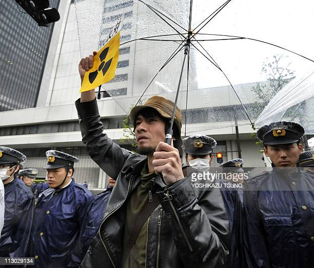 Police stand in a cordon as a protester raises a placard during an antinuclear demonstration in front of the headquarters of the Tokyo Electric Power...
