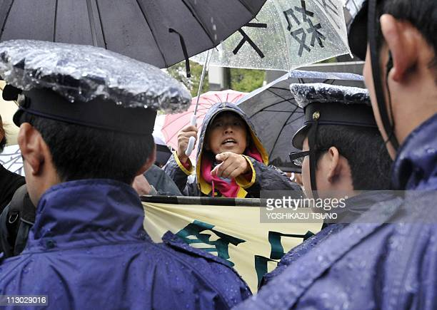 Police stand in a cordon blocking protesters during an antinuclear demonstration in front of the headquarters of the Tokyo Electric Power Company in...