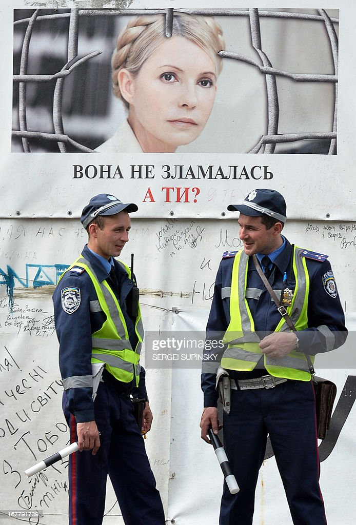 Police stand in front of a poster depicting jailed former Ukrainian prime minister and the leader of the opposition Yulia Tymoshenko signed 'She is not broken. What about You?' in the centre of Kiev on April 30, 2013. The European Court of Human Rights on Tuesday ruled that Ukraine's detention of Yulia Tymoshenko was unlawful but threw out accusations of ill-treatment. 'The Court considered that the detention had been arbitrary and unlawful during the entire period,' the judges of the Strasbourg-based court said. AFP PHOTO/ SERGEI SUPINSKY