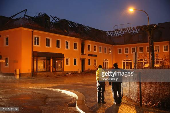 Police stand in front of the burntout remains of a former hotel that was to soon serve as a shelter for 300 asylum applicants following a fire in the...