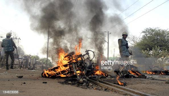 Police stand near a burning motorbike during a protest in Bhopal on December 3 2011 Thousands protested in India against the country's decision to...