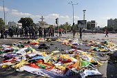 Police stand near the bodies of victims covered in flags and banners following twin explosions during a peace rally in Turkey's capital Ankara on...