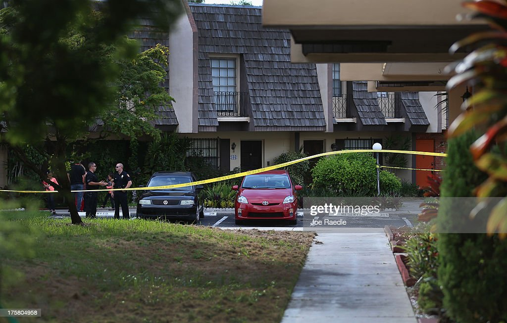 Police stand near the orange door which is the front door to a townhouse where seemingly a husband reportedly confessed on Facebook to murdering his wife on August 8, 2013 in Miami, Florida. After apparently murdering his wife and then posting a photo of her body, a South Miami man turned himself in to police. Miami Dade police spokesperson, Javier Baez, said that the police continue to investigate the scene and have been in contact with Facebook about the post. Reports indicate that the suspect is Derek Medina, 31.