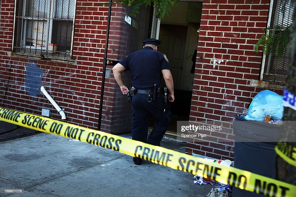 Police stand near the scene of a murder on June 4 2013 in the Brooklyn borough of New York City While shootings in New York City are down seven...