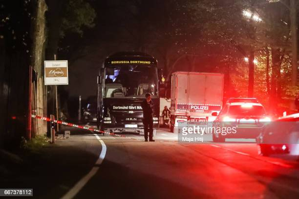 Police stand near the team bus of the Borussia Dortmund football club after the bus was damaged in an explosion on April 11 2017 in Dortmund Germany...