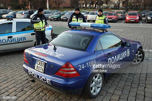 Police stand next to a Mercedes Bulgarian police car while a protest against government and police corruption took place nearby on December 5 2013 in...