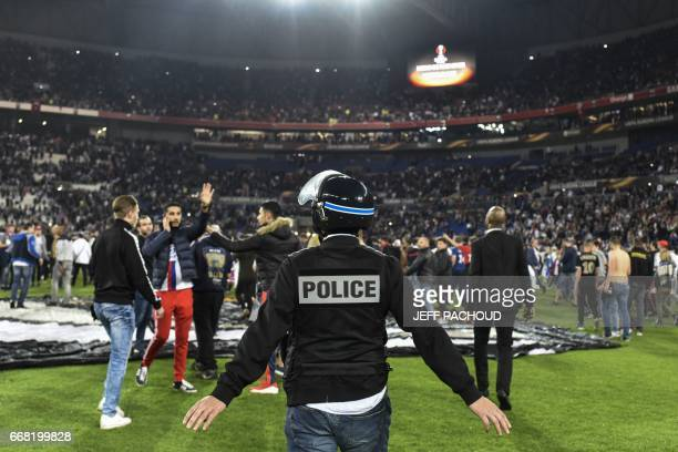 TOPSHOT Police stand on the pitch after Besiktas' and Lyon's supporters fought before the UEFA Europa League first leg quarter final football match...