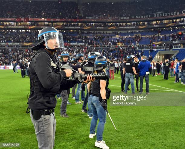 Police stand on the pitch after Besiktas' and Lyon's supporters fought before the UEFA Europa League first leg quarter final football match between...