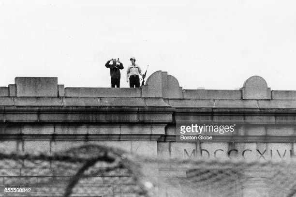 Police stand on the roof of a high school during the first day of busing desegregation in the Charlestown neighborhood of Boston Sept 8 1975