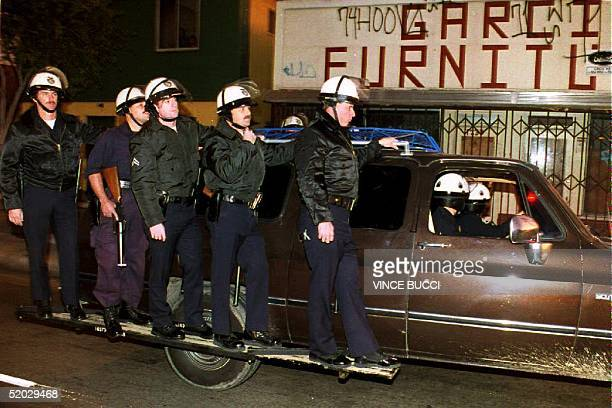 Police stand on the running boards of a specially equipped truck as they wait near the intersection of Florence and Normandie Avenues after the area...