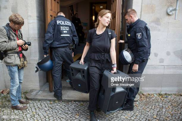 Police stand outside the Volksbuehne theater as an activist is carrying a set of speakers out of the door during negotiations to end the occupation...