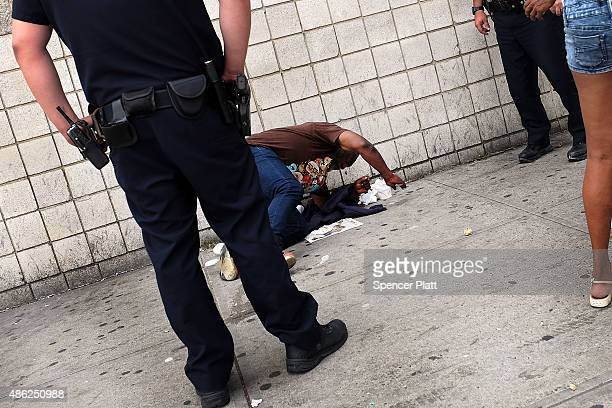 Police stand over a man passed out due to the drug K2 in an area which has witnessed an explosion in the use of K2 or 'Spice' a synthetic marijuana...