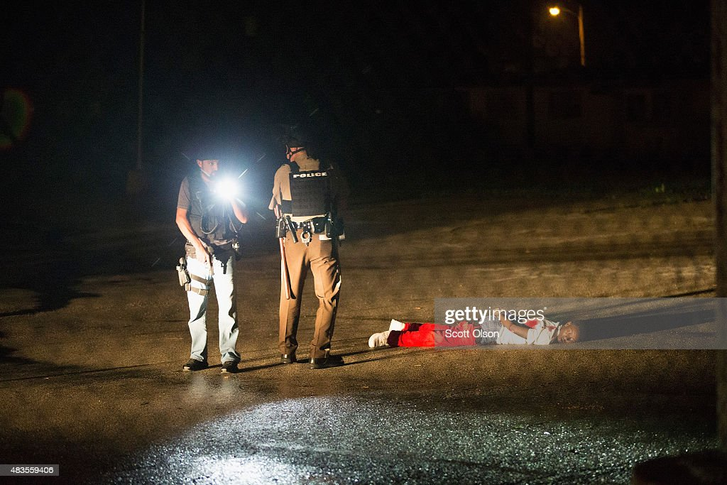 Police stand over a man with gunshot wounds lying in a parking lot after a shoot out with police along West Florissant Street during a demonstration to mark the one-year anniversary of the shooting of Michael Brown on August 9, 2015 in Ferguson, Missouri. The shooter is listed in critical condition in an area hospital. Michael Brown's death sparked months of sometimes violent protests in Ferguson and drew nationwide focus on police treatment of black suspects.