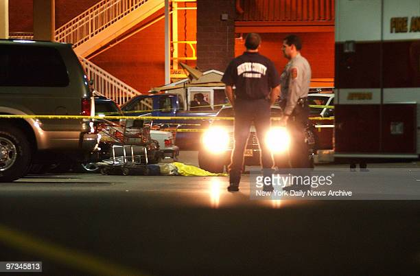 Police stand over the body of a woman who was shot to death at 915 pm outside a Home Depot store at the Seven Corners shopping center in Falls Church...