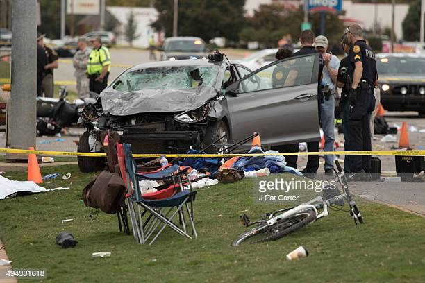 Police stand over the car that was involved after a suspected drunk driver crashed into a crowd of spectators during the Oklahoma State University...