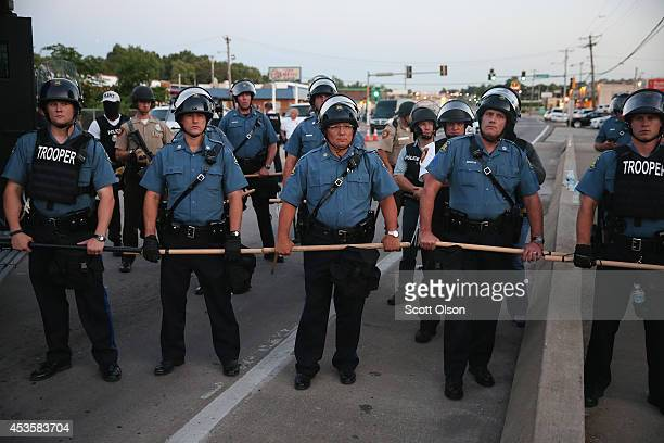 Police stand watch as demonstrators protest the shooting death of teenager Michael Brown on August 13 2014 in Ferguson Missouri Brown was shot and...