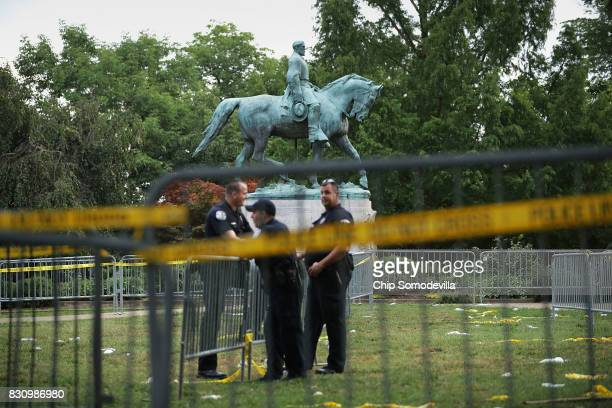 Police stand watch near the statue of Confederate Gen Robert E Lee in the center of Emancipation Park the day after the Unite the Right rally...