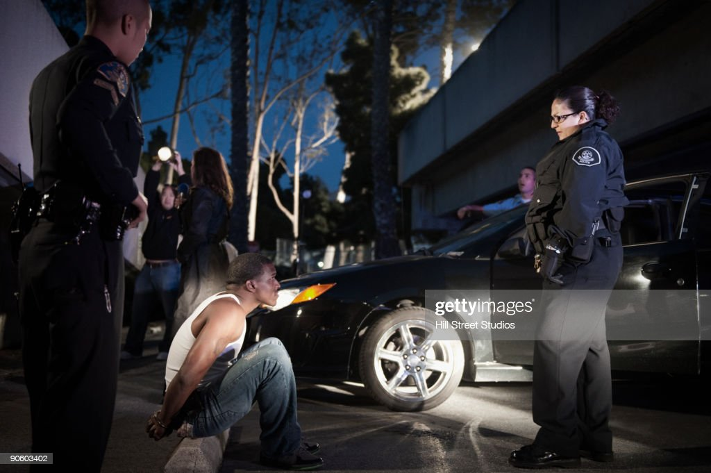 Police standing around handcuffed man sitting on curb : Stock Photo