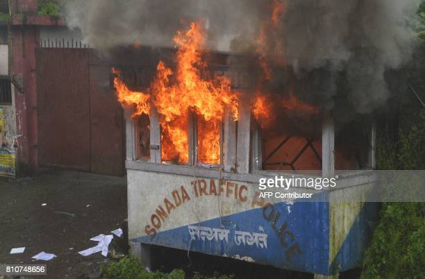 A police station is seen alight during clashes with Gorkhaland supporters during an indefinite strike called Gorkha Janamukti Morcha in Sonada near...