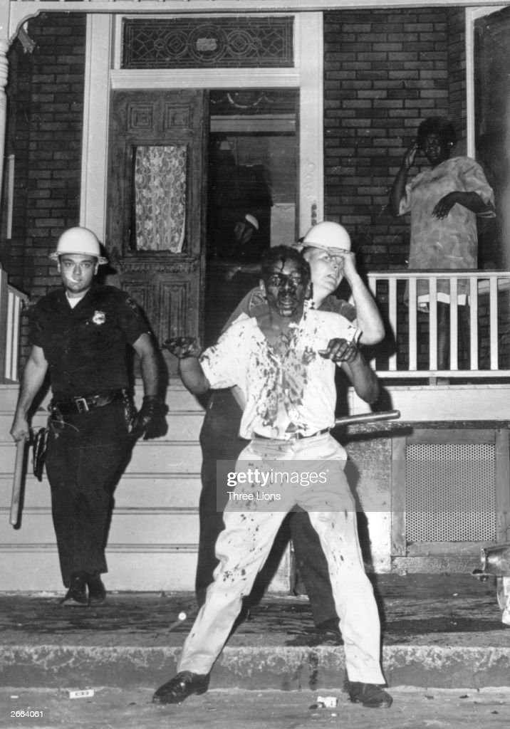 Police subdue an injured rioter during race rights riots in Newark, New Jersey.