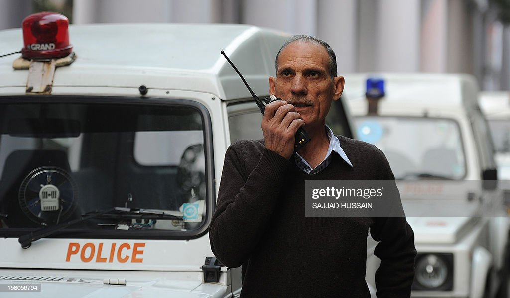 Police sub-inspector Baljit Singh Rana speaks on his walkie talkie outside his office in New Delhi on December 10, 2012. Police sub-inspector Baljit Singh Rana, a policeman for 40 years, has not taken a day off from work in the past 14 years. AFP PHOTO/SAJJAD HUSSAIN