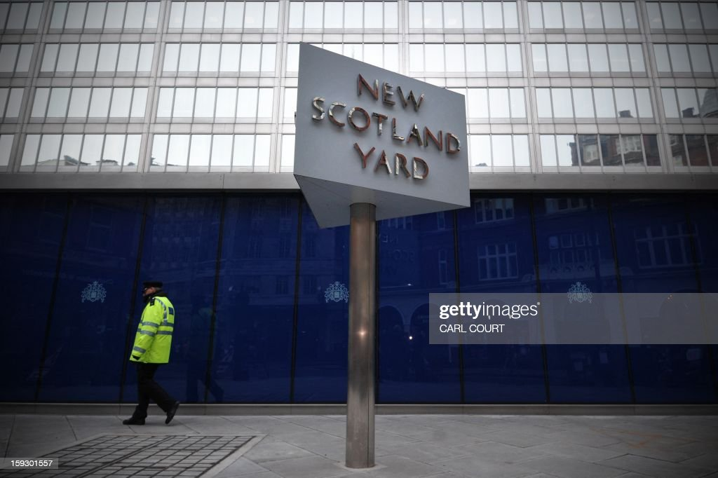 A police support officer walks past a sign outside New Scotland Yard the headquarters of the Metropolitan Police in central London on January 11...