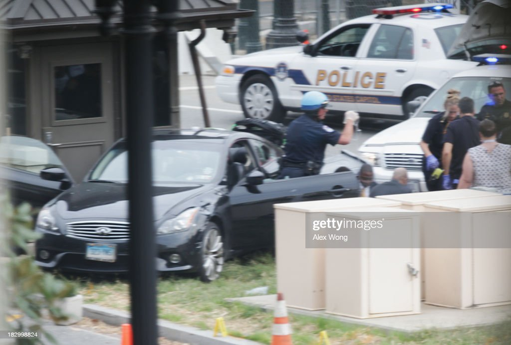 Police swarm around car on grass near the U.S. Capitol October 3, 2013 on Capitol Hill in Washington, DC. The US Capitol and the White House were placed on lockdown after an 'active shooter' situation was reported.