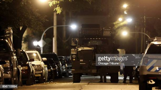 A police SWAT officer shields himself in front of an armored vehicle in the 2200 block of South Kildare Avenue which was the scene of a barricade...