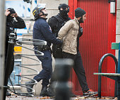 Police take a man into custody a block away from the early morning seige in the SaintDenis neighborhood in Paris France on November 18 2015 He was...