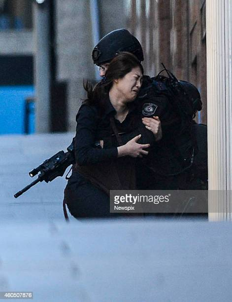 Police take hold of a hostage after she escaped during a siege at Martin Place in the CBD while hostages are held at gunpoint at the Lindt cafe in...