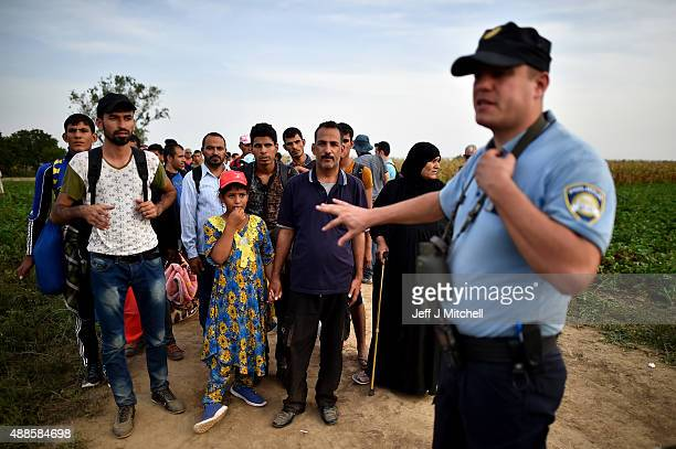Police take migrants to the border post after they walked the last few kilometres from Serbia to Croatia opening up a new route to northern EU...
