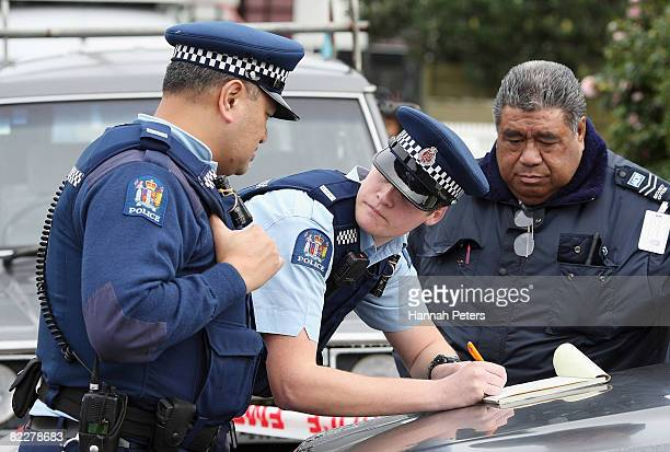 Police take notes at the murder scene of a 14 year old boy on August 13 2008 in Auckland New Zealand The 14 year old boy was killed last night...