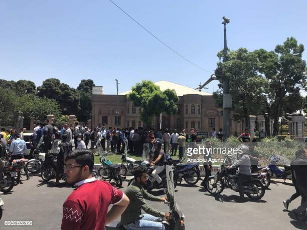 Police take security measures and people wait near the scene after gunmen opened fire at Irans parliament and the shrine of Ayatollah Khomeini in the...