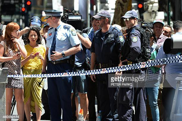 Police talk to the public near a cafe in the central business district of Sydney on December 15 2014 A gunman was holding terrified hostages inside a...