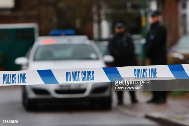 Police tape is pictured as police officers stand guard outside of a house in Edgeware on December 27 2007 in London England A man is facing charges...