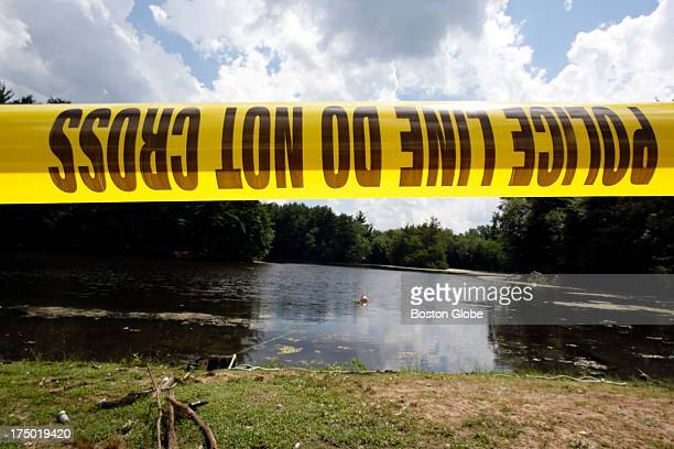 Police tape is seen in front of Pine Lake as Connecticut State Police officers search the Lake looking for a gun that police believe was used to kill...